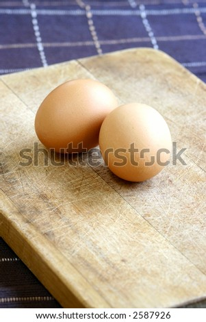 Two fresh eggs on wooden chopping board.