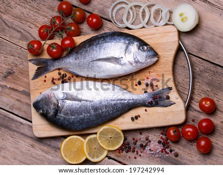 Two fresh gilt-head bream fish on cutting board with lemon, onion and tomato. Horizontal.