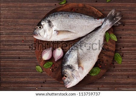Two fresh gilt hear sea bream on round wooden chopping board with fresh basil leaves, colorful peppercorn and onion, top view. Seafood coocking ingredients in natural brown.