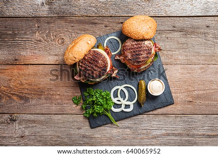 Two fresh homemade burgers on dark slate stone board, pickles, sauce and sliced onion over wooden background. Top view, copy space