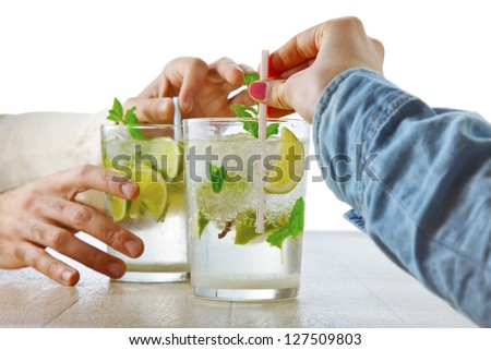 Two fresh mojitos cocktail. A couple taking mojitos with mint leaves and lime