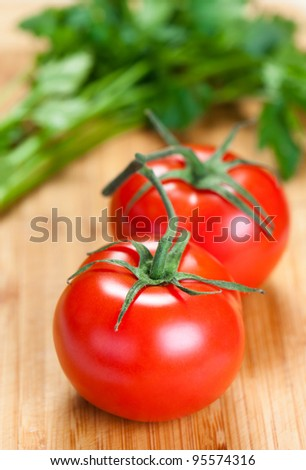 Two fresh ripe red tomatoes on a wooden surface ready for use as cooking ingredients.