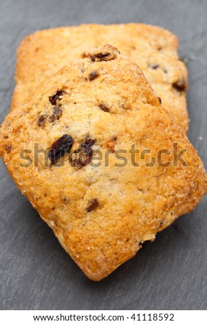 Two fresh scones on a slate background