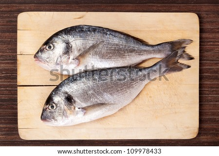 Two fresh sea bream fish on used wooden cutting board on brown background. Culinary seafood eating in natural brown.