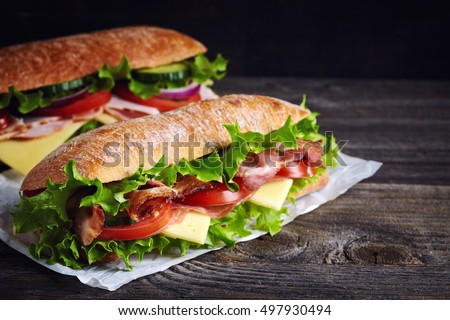 Shutterstock Two fresh submarine sandwiches with ham, cheese, bacon, tomatoes, lettuce, cucumbers and onions on dark wooden background