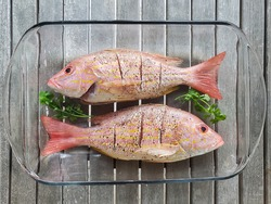Two fresh, whole lane snapper prepared for cooking.