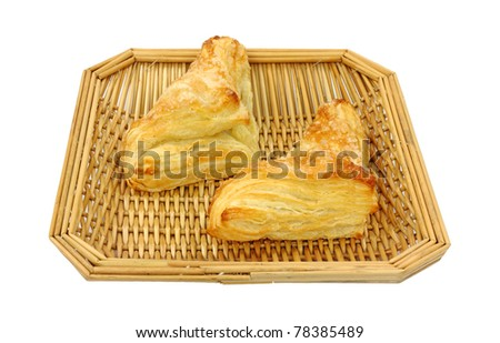 Two freshly baked apple turnovers in a wood wicker basket on a white background.