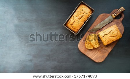 Photo of Two freshly baked homemade pumpkin bread loaves with knife over dark background. Image shot from top view, flatlay.