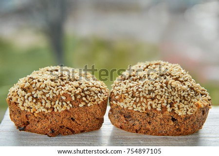 Two freshly baked raisins cakes with sesame seeds isolated on gray wooden table. Two muffins on blurred nature background. Close up view #754897105