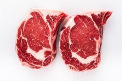 Two freshly cut boneless ribeye steaks on a butchers table