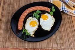 Two fried eggs prepared with unbroken yolks, served sunny side up and grilled long thin sausage on the black dish on the bamboo table mat