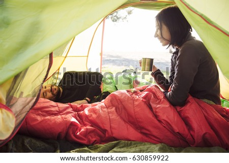 Two friend traveling and spending time in tent while drinking coffee in the morning. Happy people in camping. View from inside. Couple of travelers  #630859922