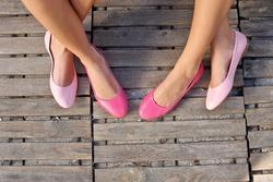 two friend women sitting cross legged wearing pink flats