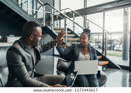 Two friendly smiling african business people celerbarting their sucess with a high five