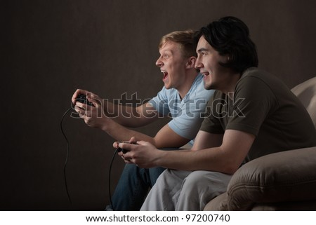 two friends are focused on playing video games on gray background