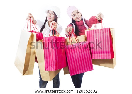 Two friends are holding shopping bags in winter clothes, isolated in white