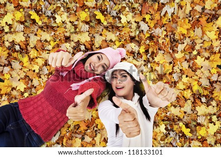 Two friends are laying on Autumn leaves