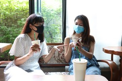Two friends Asian women wearing hygienic mask sitting and making conversation at wooden table in cafe. Social distance to prevent from covid-19.