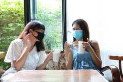 Two friends Asian women wearing hygienic mask sitting at wooden table in cafe. Social distance to prevent from covid-19.