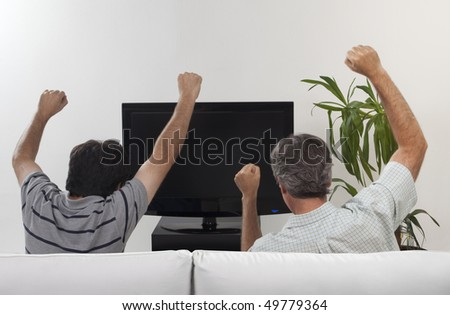 Two friends celebrating some event watching a flat tv set sitting on a sofa - stock photo