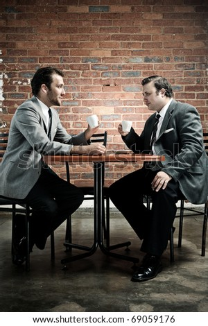 Two friends discuss the taste of coffee while wearing suits