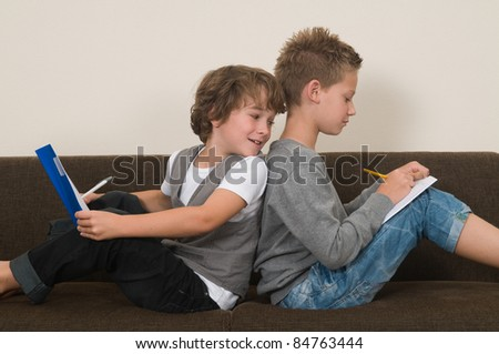 Two friends doing their homework in the livingroom on the couch