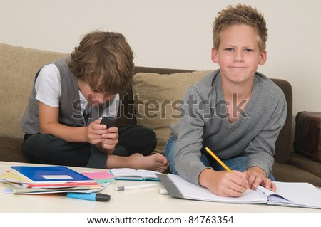 Two friends doing their homework in the livingroom. One of them is gaming, the other one is not ready and is jealous.