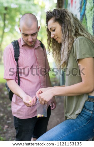 Two friends enjoying rolling a joint and smoking it in the park. #1121153135