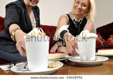 Two friends enjoying their coffees at a coffee shop.
