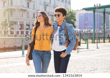 Two friends having a casual chat while walking on street. Two multiethnic girls laughing and walking in the city centre. Brazilian young woman and stylish latin girl wearing sunglasses.