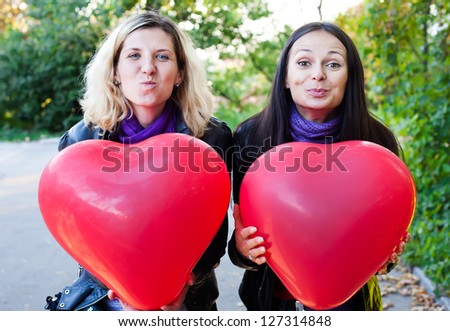 Two friends holding balloons in the form of heart