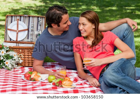 Two friends holding glasses while looking into each others eyes and lying on a blanket with a picnic basket