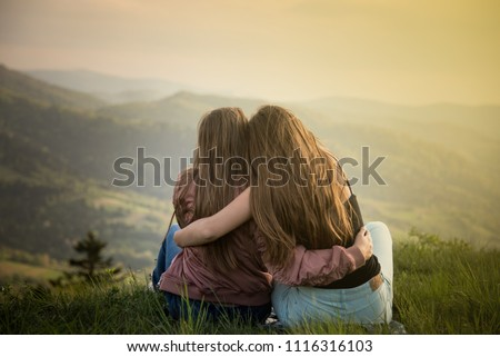 Two friends hugging looking at the Carpathians mountains. Two girls on top of the mountain watching at sunset. ストックフォト ©