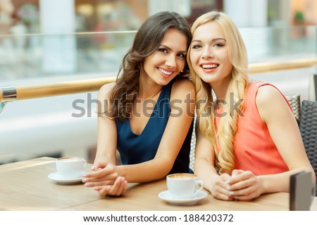 Two friends in cafe. Two young female friends sitting in cafe and looking at camera