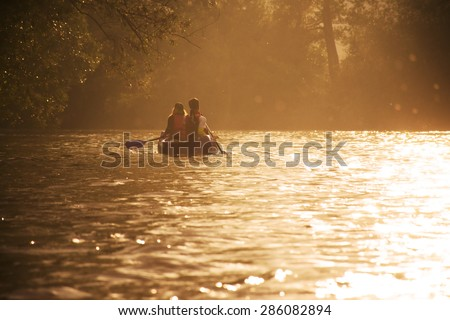 Two friends in canoe are swimming on the river in beautiful last evening light