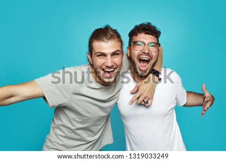 Two friends in casual wear standing and laughing together. Best friends enjoying isolated over blue background. Two men having fun isolated over blue wall. #1319033249