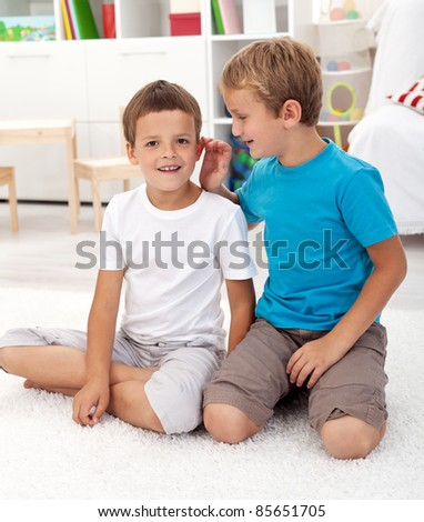 Two friends in the kids room talking secrets and having fun
