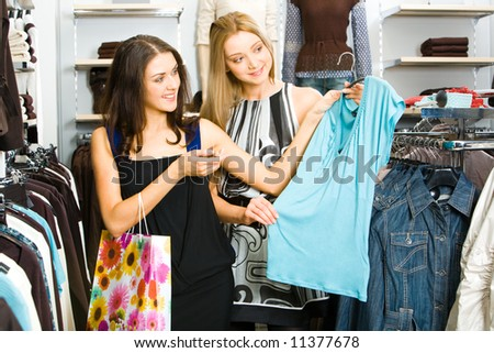 Two friends looking at new T-shirt and choosing new clothes