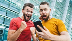 Two friends looking extremely excited getting good news about winning a bet in online bookmaker watching broadcast with winner results on mobile phone. Football stadium on the background.