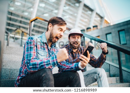 Two friends looking extremely excited getting good news about winning a bet in online bookmaker watching broadcast with winner results on mobile phone. Football stadium on the background. #1216898989