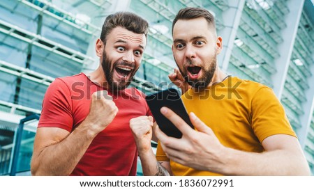 Two friends looking extremely excited getting good news about winning a bet in online bookmaker watching broadcast with winner results on mobile phone. Football stadium on the background. Сток-фото ©