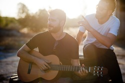 Two friends playing guitar