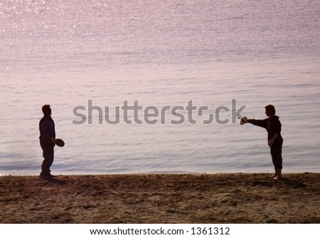 Two friends playing tennis in the Beach at Sunset. Palma of Majorca (Balearic Islands - Spain)