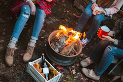 two friends relax comfortably and drink wine on an autumn evening in the open air by the fire in the backyard. The concept of autumn, friendship. top view of the legs