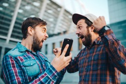 Two friends showing sincere emotions of joy about victory in online lottery. Men being happy winning a bet in online sport gambling application with football stadium on the background.