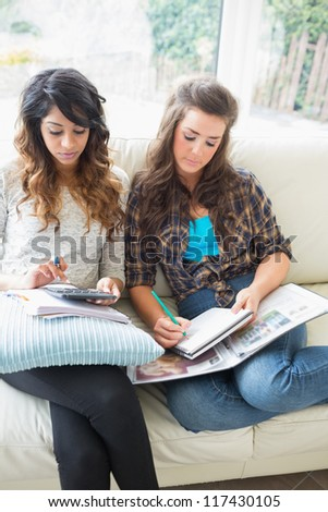 Two friends sitting in a couch doing homework with notepads and calculator