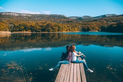 Two friends sitting on peer and enjoying lake view in autumn. Good sunny day for resting outdoors and travel.