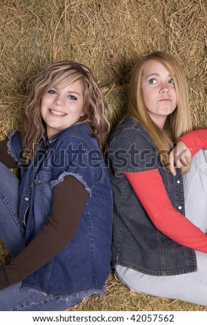 Two friends sitting on the hay one smiling and the other with a funny expression on her face.