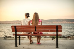 two friends sitting on wood bench near beach on evening sunset
