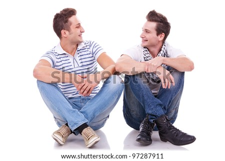two friends smiling to each other while sitting on a white background